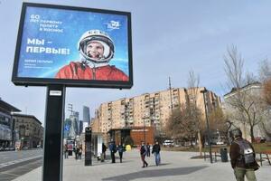 宇宙飛行士ガガーリンの写真の横に「私たちが最初だ!」と書かれたポスター=12日、モスクワ(共同)
