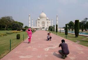 21日、入場が再開されたインドの世界遺産タージマハルで写真を撮る観光客ら(ロイター=共同)