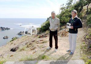 ささゆり祭り開催に向けドローンで島内の風景を撮影する神野さん(左)ら=阿南市の伊島