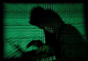 フードをかぶり、ノートパソコンでサイバー攻撃をする男のイメージ写真(ロイター=共同)