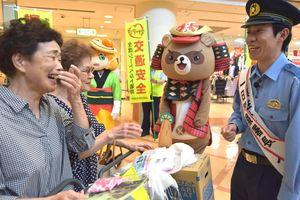 買い物客に特殊詐欺への注意を呼び掛けるみっとしーさん(右)=小松島