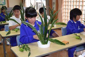 オモトを使った生け花に挑戦する児童=那賀町の相生小学校