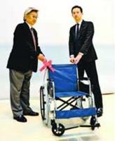 西尾営業所長右から車いすを受け取る笹田館長=徳島市のふれあい健康館
