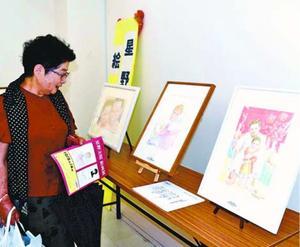 作品を見つめる来場者=徳島市のポッポ街商店街