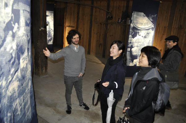 メルカドさん(左端)の説明を受けながら藍染で描いた作品に見入る来場者=神山町神領の旧名西酒造酒蔵
