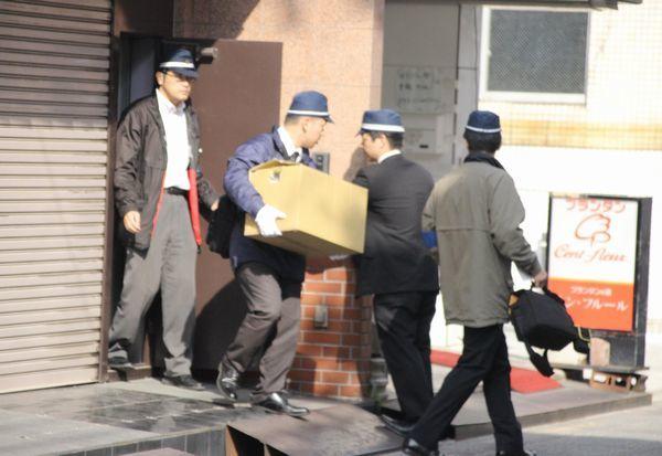 小田興業の事務所の家宅捜索を終え、段ボール箱を運ぶ県警捜査員=午前10時45分ごろ、高松市