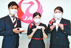 応援メッセージ入りカードを作っている(左から)藤川マネジャー、桒島さん、森永さん=松茂町の徳島阿波おどり空港