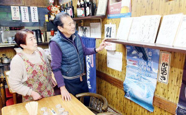 大杉さんのサイン色紙を眺める「あそこ食堂」の細川さん夫妻=鳴門市撫養町南浜