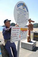 観察のマナーなどを記した看板を設置する町ウミガメ保護監視員=美波町の大浜海岸