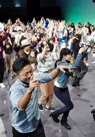 ステージに上がり、踊り子と阿波踊りを楽しむ来場者たち=徳島市のアスティとくしま