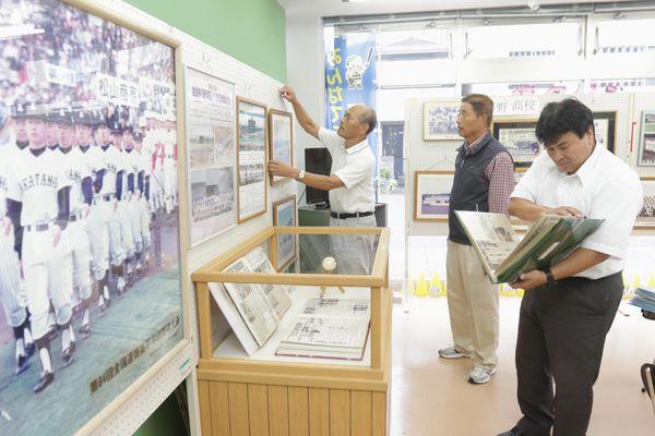 新野高校野球部の活躍を振り返る企画展の準備をする市職員ら=阿南市富岡町の展示場「キラキラあなん」