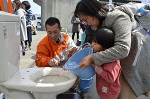 断水時のトイレの流し方を学ぶ参加者=北島町の県立防災センター