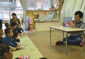 紙芝居の読み聞かせを行う三谷さん(右)=徳島市の四国大付属西富田保育所