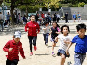 ランニング教室で小学生と一緒に走る尾崎さん=徳島市の内町小学校