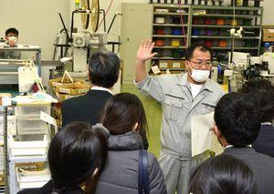 工場で社員から説明を受けるバスツアー参加者=小松島市田野町の相生電子