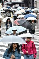 傘を差し、職場や学校へ向かう人たち=午前7時50分ごろ、徳島駅前