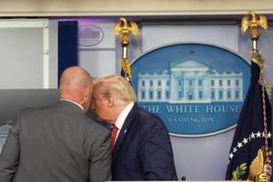 10日、米ホワイトハウスで大統領警護隊(シークレットサービス)と言葉を交わすトランプ大統領。この後、記者会見室を退席した(ロイター=共同)