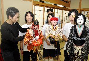阿波木偶箱まわし保存会の会員(左端)に人形の持ち方を習う生徒=東みよし町昼間の町中央公民館