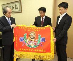 植田社長(左)から新調された優勝旗を受け取る県中体連の河野会長(中)と佐藤理事長=徳島新聞社