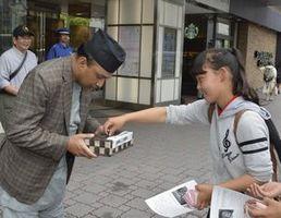 ネパール大地震の復興支援募金に協力する通行人=徳島駅前