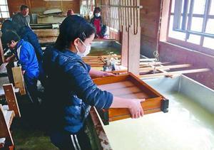 卒業証書の拝宮和紙を漉く児童=那賀町拝宮の中村さんの工房