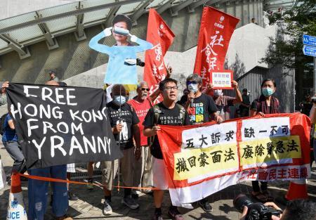 香港立法会の周辺で、「五大要求」全ての実現や「覆面禁止法」の撤回を求める人たち=16日(共同)