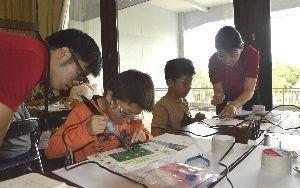 はんだごてを使って3色のLEDなどを取り付ける子どもたち=徳島市のあわぎんホール