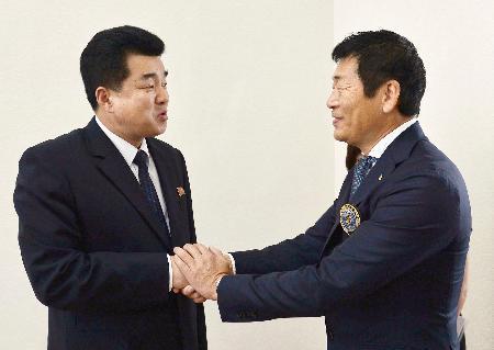 平壌で北朝鮮オリンピック委員会委員長の金日国体育相(左)と握手する国際体操連盟の渡辺守成会長=13日(共同)