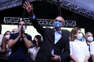 5日、ドミニカ共和国の大統領選で初当選し、支持者に手を振るアビナデル氏(中央)(ロイター=共同)