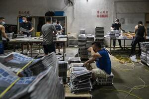 22日、香港の蘋果日報の印刷所で、新聞をまとめる作業員(ゲッティ=共同)