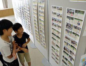 熱戦の様子を捉えた写真に見入る子どもたち=阿南市富岡町の市文化会館