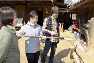 手作りのアースオーブンでピザを焼く岩佐さん(右)=佐那河内村上