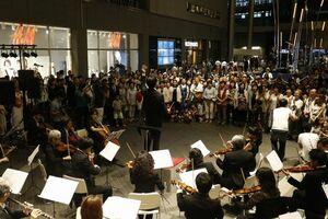 「第九」のアジア初演100年をPRするフラッシュモブを披露する合唱団と楽団=東京都世田谷区の二子玉川ライズ