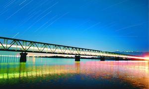 通過する列車の明かりで闇に浮かぶ吉野川橋梁=徳島市応神町