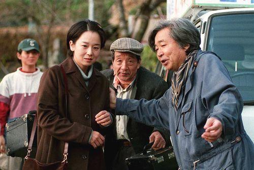脇町でのロケに臨む田中裕子さん(左から2人目)らに指示する山田監督(右端)=1996年11月