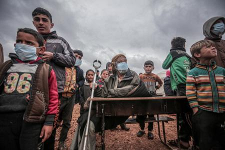 シリア北西部イドリブ県で、新型コロナウイルスの予防措置の説明を受ける人々=20日(ゲッティ=共同)