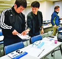 配布されたナンバーカードなどを確認する郡市関係者=徳島新聞社