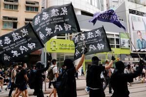 香港で、独立を求める旗を掲げ香港国家安全維持法に抗議する人々=1日(ロイター=共同)