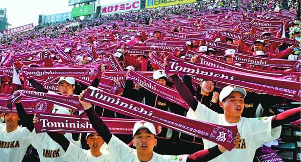 校名入りのタオルを掲げて高らかと校歌を歌う富岡西の応援団=3月26日、甲子園球場