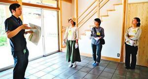 神山町職員左に案内され、家族用の部屋を見学する参加者=同町神領