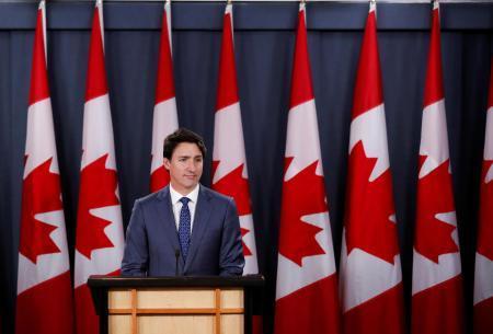 23日、カナダ・オタワで記者会見するトルドー首相(ロイター=共同)