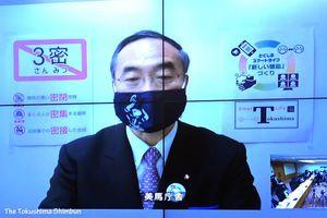 リモート中継で臨時記者会見を行う飯泉知事=27日午後5時半ごろ、徳島県庁