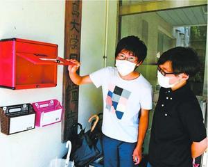 徳島大の学生寮入り口にある郵便受けをのぞく大学生。約70人が暮らす同施設には布マスクが1セットしか届かなかった=徳島市城南町1