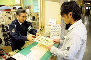阿波吉野川署員(左)からチラシを手渡される事業者=吉野川市川島町の同署