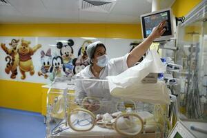 5日、モロッコ・カサブランカで、マリの女性が出産した九つ子のうちの1人を世話する看護師(ゲッティ=共同)