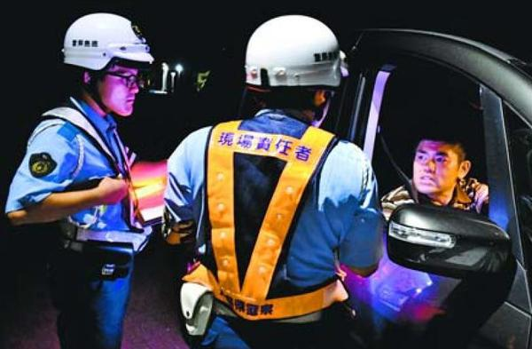 死亡ひき逃げ事件の現場を通行するドライバーに情報提供を求める署員=阿波市吉野町西条