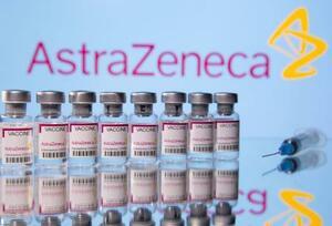 アストラゼネカのロゴを背景に「新型コロナウイルスのワクチン」のラベルが貼られた瓶(ロイター=共同)