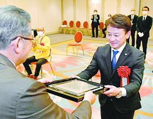 米田社長(左)から大賞の賞状を受け取る徳島ヴォルティスの岸田社長=JRホテルクレメント徳島