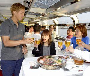 大松サッカー少年団の関係者と歓談する塩谷選手(左端)=徳島市の新町川