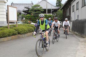 四国霊場の歴史に触れながらサイクリングを楽しむ参加者=徳島市国府町の井戸寺前